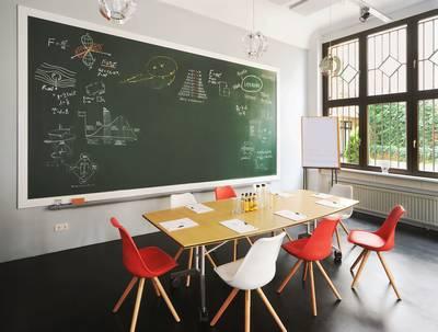 Ein Meetingraum mit Tisch für 8 und großer Tafel